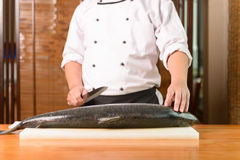Chef preparing a fresh salmon fish on a cutting board, Japanese chef Royalty Free Stock Photos