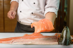 Chef preparing a fresh salmon fish on a cutting board, Japanese chef Royalty Free Stock Photography