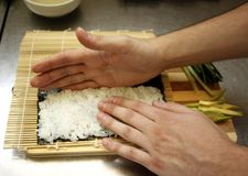 Chef preparing maki sushi by rolling nori seaweed,rice and fish on makisu bamboo mat. royalty free stock photos