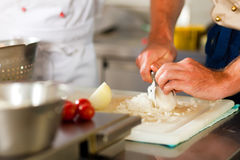 Chef preparing onion in restaurant or hotel kitchen. Close up of chef in a commercial restaurant or hotel kitchen working, he is preparing an onion and royalty free stock photos