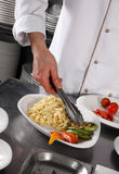 Chef preparing pasta. On professional kitchen in restaurant Stock Photo