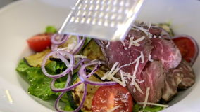 Chef preparing a salad. Spread tomatoes, onion falls. Slow motion
