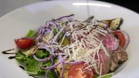 Chef preparing a salad. Spread tomatoes, onion falls.Slow motion