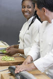 Chef Preparing Salmon By Colleague. Side view of a male chef preparing salmon beside colleague in kitchen stock images