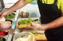 A chef preparing a sandwich with fresh salad. Ham, cheese and butter. Close up of the hands holding the bread roll Stock Photo