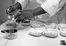 Chef preparing sauce on table with white cloth, black and white. Chef preparing sauce, many small dishes on table Royalty Free Stock Photos