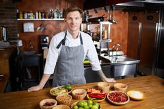 Chef Preparing Spicy Dish. Portrit of handsome chef posing standing at table with spices, copy space stock image