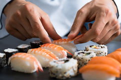Chef preparing sushi. Closeup of chef hands preparing japanese food. Japanese chef making sushi at restaurant. Young chef serving traditional japanese sushi Stock Photography