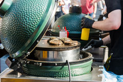 Chef preparing tasty burgers at outdoor stand. Royalty Free Stock Image