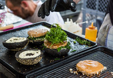 Chef preparing tasty burgers at outdoor stand. Stock Photography