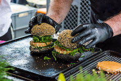 Chef preparing tasty burgers at outdoor stand. Royalty Free Stock Images