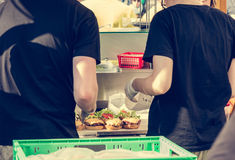 Chef preparing tasty burgers at outdoor stand. Stock Photos