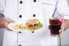 Chef present a burger and cola drink Royalty Free Stock Photography