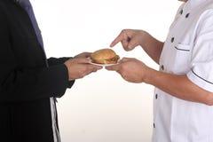 Chef present Hamburger to custome Stock Photo