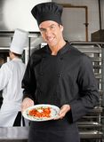 Chef Presenting Dish In Kitchen Royalty Free Stock Image