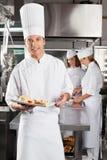 Chef-Presenting Dish In-Werbungs-Küche Stockfotografie