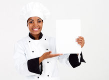 Chef presenting menu. Half length portrait of african american female chef presenting menu over white Royalty Free Stock Photography