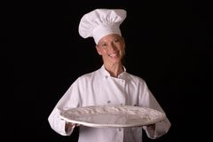 Chef Presenting Platter. Assertive posed female Chef in uniform presenting a platter Stock Photo