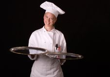 Chef Presents Silver Platters. Assertive posed female Chef in uniform proudly presenting two silver platters Royalty Free Stock Photography