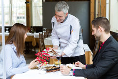 Chef presents them the second course to a couple in the restaurant. Stock Photo