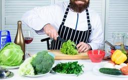 Chef principal d'homme ou nourriture à cuire amateur Couteau pointu coupant le légume Préparez l'ingrédient pour la cuisson Selon images libres de droits