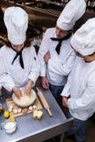 Chef principal enseignant son équipe à préparer une pâte Photos stock