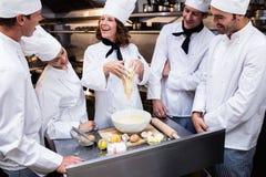 Chef principal enseignant son équipe à préparer une pâte Images stock