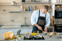 A chef in a process - preparing Italian dish. Kitchen interier Royalty Free Stock Photography