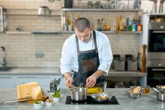 A chef in a process - preparing Italian dish. Kitchen interier Royalty Free Stock Image