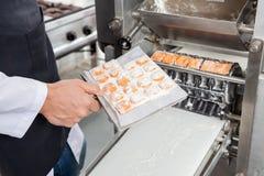 Chef Processing Ravioli Pasta in automatisierter Maschine Stockbild