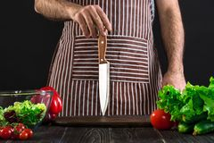 Chef. Professional chef knife including assorted fresh vegetables. On black background Stock Photos