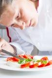 Chef professionnel préparant le plat avec les tomates et le mozzarella Photos libres de droits