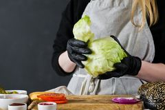 The chef pulls the lettuce. The concept of cooking a black Burger. Homemade hamburger recipe. Kitchen, side view, space for text. royalty free stock photography