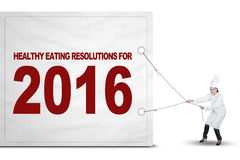 Chef pulls a text of healthy eating resolutions. Picture of female chef wearing uniform and pulls a big board with a text of healthy eating resolutions for 2016 Royalty Free Stock Photography