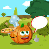 Chef pumpkin with pizza showing thumb up on a meadow with speech bubble Royalty Free Stock Photos