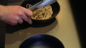 Chef put the udon noodles into a bowl. Chef put prepared udon noodles into a bowl. The last step of preparing traditional korean dish. Close-up stock video