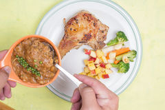 Chef puted gravy sauce to pork chop steak Royalty Free Stock Photography
