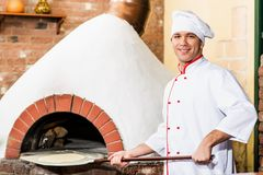 Chef puts dough in the oven for pizzas, Royalty Free Stock Photos