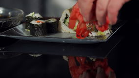 Chef puts ginger on the sushi plate, close-up. stock footage