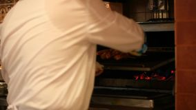 Chef puts meat skewers in the oven. Camera shift stock footage