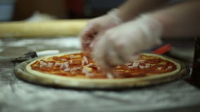 The chef puts the pieces of ham on dough stock video