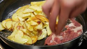 Chef puts the pieces of meat in the pan, where the potatoes are fried in oil stock video footage