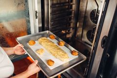 Chef puts strudel on baking sheet in the oven Royalty Free Stock Photos