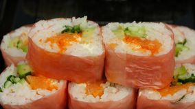 Chef puts sushi in pink norrie in a bowl. Close up. Rolls with various fillings are cooked for catering, chef prepared the rolls in pink nori, people by sushi stock video footage