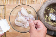 Chef puttinfg salt to chicken wings for cooking Royalty Free Stock Image