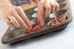 Chef putting bacon into muffin baking pan Royalty Free Stock Image