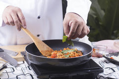 Chef putting basil to pan for cooking spaghetti chicken sauce Royalty Free Stock Photos