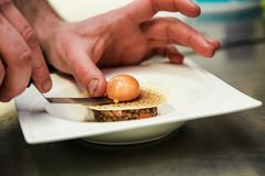 A chef putting a boiled egg on a meal in a French gastronomic restaurant Stock Photos