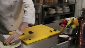 Chef putting curved cucumber into the plate, medium shot. Chef in restaurant putting curved cucumber into the plate, medium shot stock footage