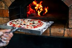 A chef is putting the delicious pizza to a stove for baked yummy pizza. It's famous italian food. stock photos